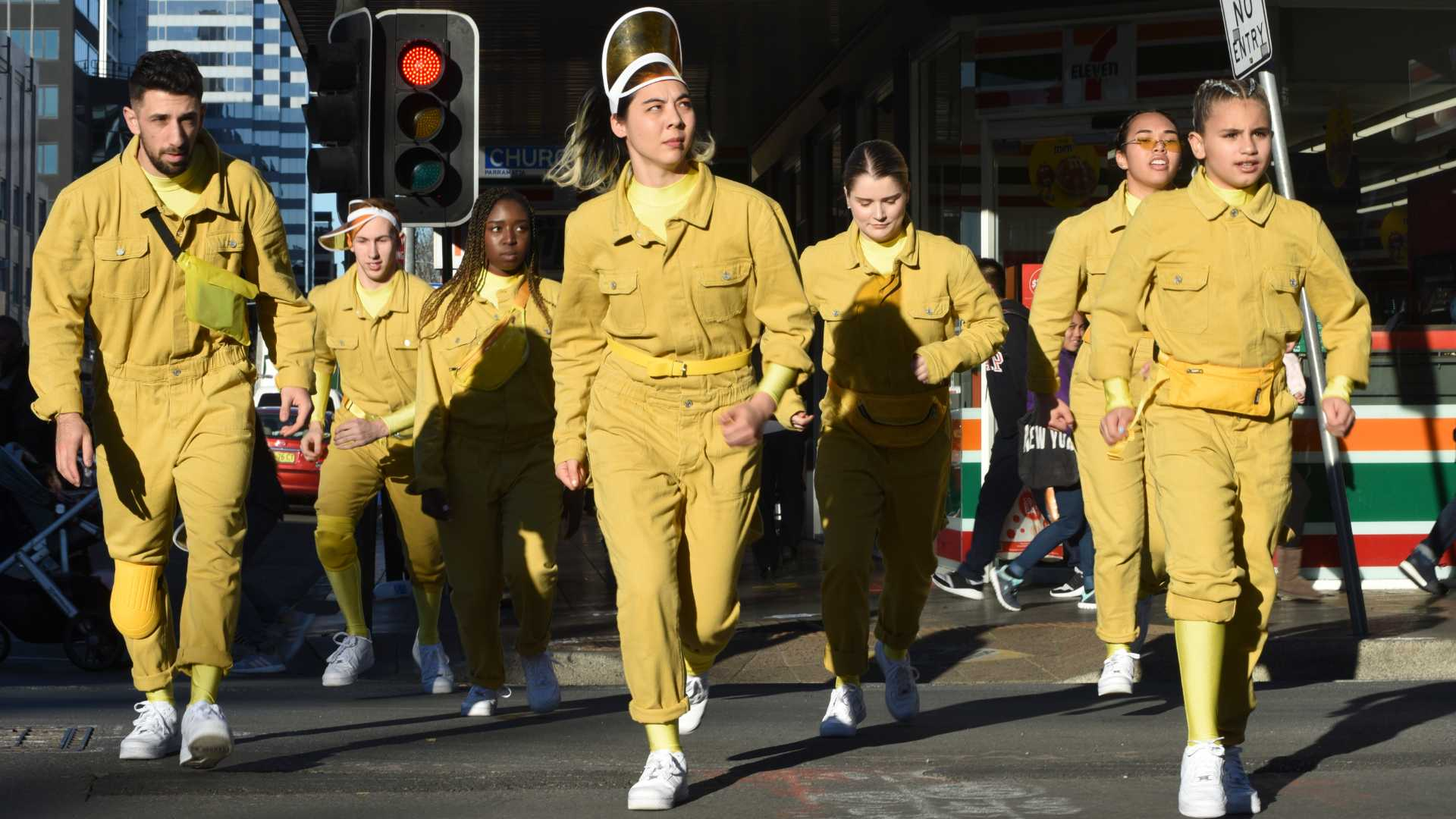 Performers wearing yellow jumpsuits walking in the street
