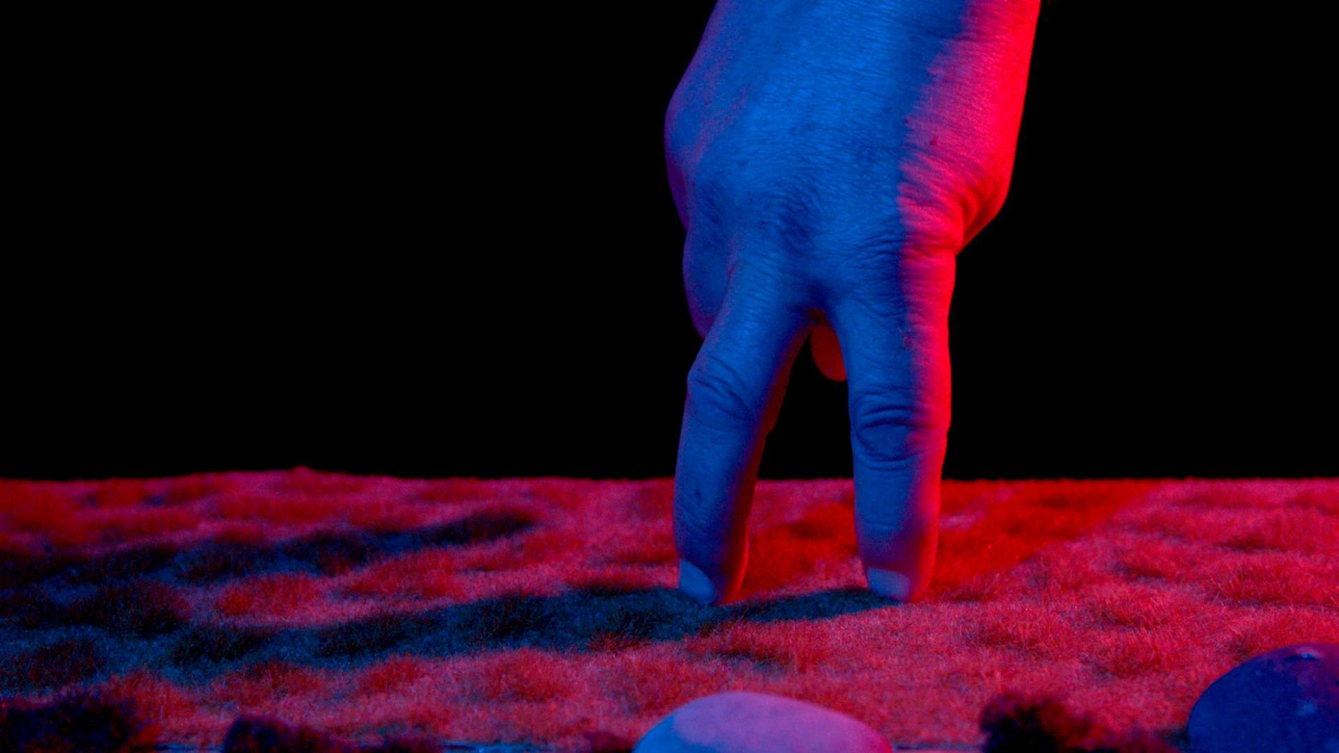 Video still featuring hand with two fingers and shadow, coloured by blue light and pink surface